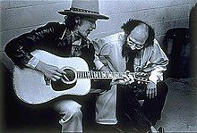 Dylan, wearing a hat and leather coat, plays guitar and sings, seated. Crouched next to him is a bearded man, listening to him with head bent.