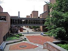 A brick courtyard is flanked by three-story brick buildings with a black glass bridge between them. Trees are visible to the right.