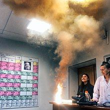 An instructor and a student look at clouds of smoke and a bright flame produced on the edge of a table.