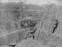 一个挖开的深坑,一名工人靠在坑壁上。