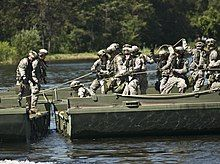 A group of soldiers in green fatigues assembling a bridge