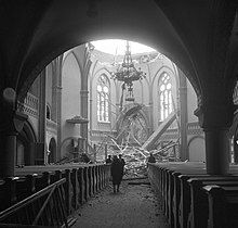 The dome of the Vyborg Cathedral has collapsed after Soviet bombing. Four people stand in the nave and look at the rubble, highlighted by sunlight shining through the damaged dome.