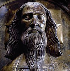 Bronze effigy of man's face with flowing shoulder-length hair and long moustache and beard
