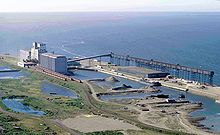 An industrial seaport sits on the coast of a large body of water