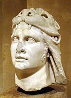 Slightly damaged stone sculpture of a man's head. He wears an animal pelt over his hair.