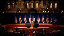 A speaker at a podium in the center of a stage decorated with nine American flags and a red carpet.