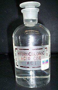 """透明带有玻璃塞的玻璃瓶,上面贴着标签:""""HYDROCHLORIC ACID. COX. HCl"""""""