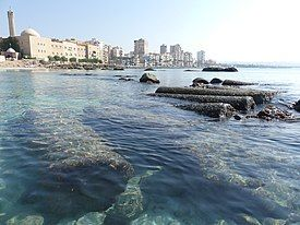 Submerged ancient columns with the skyline of the modern city in the background.