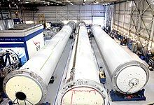 Long, cylindrical rocket sections lie in a warehouse