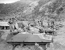 Black and white photograph of men wearing military uniforms standing on top of tanks parked on a grassed area