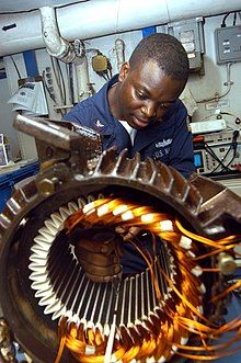 US Navy 040902-N-7683J-003 Electrician's Mate 3rd Class Tayo Gbadebo from Lagos, Nigeria, rewires the motor from an Aqueous Film Forming Foam (AFFF) Sprinkler System's pump.jpg