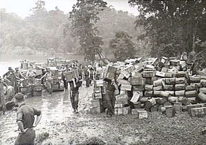 Black and white photo of a large number of small wooden crates stacked on muddy ground, with men wearing military uniforms carrying additional small wooden crates