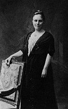 A posed formal black-and-white photograph of a woman standing behind a chair upon which she is resting her hand
