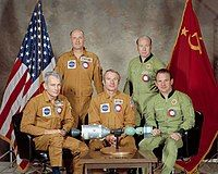 the five crew members of ASTP sitting around a miniature model of their spacecrafts