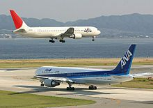 A white and red-tailed Japan Airlines aircraft above the runway, with landing gears down, and an All Nippon Airways in blue and white livery taxiing