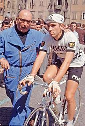 Eddy Merckx being pushed while on bike before a stage.