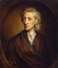 Half-length portrait of a man with a shock of neck-length white hair who is wearing a loose brown robe and white shirt.