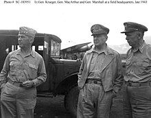 Three men in Army uniforms with open neck shirts. Krueger wears a garrison cap, MacArthur his special cap, and Marshall, a peaked cap. in the background there is a truck and a propeller-driven airplane.