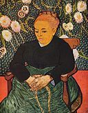 An elderly well-dressed woman sits facing to her right (the viewer's left). She has her hands clasped together on her lap, and she is dressed in a dark top and green dress in front of a vivid flower wallpaper background.