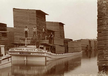 A flat boat with large, wooden boards piled on it floats in a narrow channel surrounded by more piles of wooden boards. A few men pose on the boat.