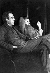 Two men sitting, looking relaxed. A dark-haired Bohr is talking while Einstein looks skeptical.