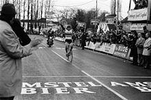 A cyclist holding his hands aloft.