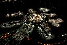 The building of an airport at night with a large central building with several lit spokes of the terminals.
