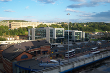 Sheffield Interchange, the main hub for bus and coach operations in Sheffield. In the foreground is the interchange itself. Visible in the bottom left corner is the new, main entrance to the interchange. In the centre are the long bus stands that form the interchange. Above that is the Digital Campus commercial development built upon an unused section of the interchange. In the top left corner is the 1960s Park Hill flats development and to the right is Sheffield Railway Station.