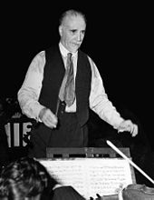 elderly, balding man with short white moustache and beard, conducting an orchestra