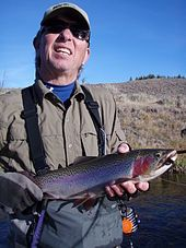 Photo of fisherman holding a rainbow trout