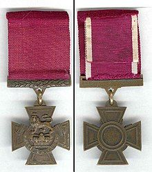 """The obverse and reverse of the bronze cross pattée medal; obverse showing the crown of Saint Edward surmounted by a lion with the inscription """"for valour"""" with a crimson ribbon; the reverse shows the inscription of the recipient on the bar connecting the ribbon with the regiment in the centre of the medal."""