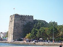 Photograph of a tall, roughly square stone fortress in a modern coastal city.