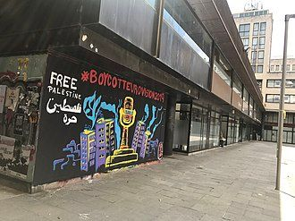 """A painted mural on a wall on a street in Girona, Spain: the Eurovision trophy appears covered in barbed wire surrounded by tower blocks, with the words """"#BoycottEurovision2019"""" above, and """"Free Palestine"""" in English and Arabic to the top left"""