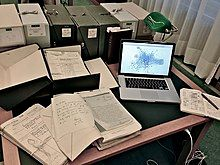 A laptop computer next to archival materials