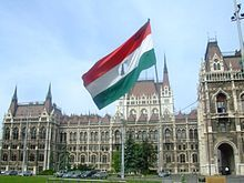 Tricolor Hungarian flag with circle cut from the middle flying atop a bent flagpole in front of a large Neogothic building