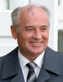 A man in a grey suit, white shirt and dark tie, balding with grey hair, he has a birthmark on his forehead