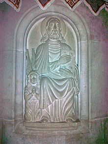 A relief depicting Jesus holding a book and a small angel praying besides him