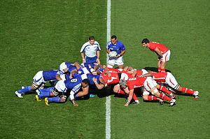 A player holds a ball in front of two opposing groups of eight players. Each group is crouched and working together to push against the other team.