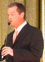 A man with dark hair wearing, including a black suite with a pink tie.