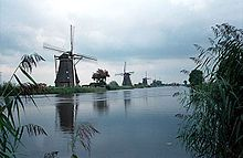 Typical Dutch scene with a series of windmills along the waters edge