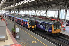 Two trains – one modern, and one from the eighties – in a Victorian railway station.