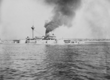 Black-and-white photo of a ship with a single funnel sailing to the left.