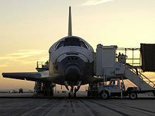 The Space Shuttle Discovery on the runway as ground crews work to get the crew out of the orbiter