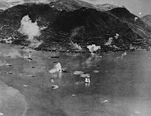 Aerial photo of an island with an urban area along its shore and a steep mountain in the center. Many ships are in the water next to the island, and plumes of water are erupting near some of them.