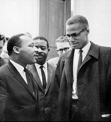 Malcolm X and Martin Luther King Jr. speak to each other thoughtfully as others look on.
