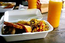 A Styrofoam container of food, plastic fork, and glass of juice