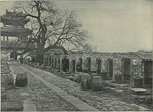 A black-and-white picture of a stone-paved alley going from bottom right to top left leading to a three-roofed gate and bordered on the right by a line up of small roofed cubicles open on one side.