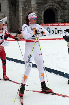 Skier in white kit with blue sunglasses with a stone building in the background.
