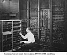 Man replacing one vacuum tube out of hundreds in early computer
