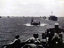 A group of World War II-era ships at sea photographed from another ship. Two men wearing helmets are in the foreground.